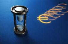 蓝色背景下欧元符号与沙漏